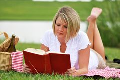 Woman on Picnic with Book and Wine. Young blond woman on picnic with book, picnic basket and wine.  Gingham blanket and napkin Royalty Free Stock Images