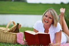 Woman on Picnic with Book and Wine. Young blond woman on picnic with book and wine.  Picnic basket with gingham blanket and napkin Stock Photos