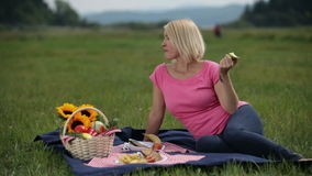 Woman at picnic eating an apple. Young blonde female eats an apple on picnic stock footage