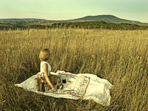 Woman on a picnic in field Royalty Free Stock Image
