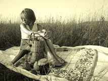 Woman on a picnic in field. Woman sitting in a grassy field on a blanket with a woven bag and food, sepia-toned Royalty Free Stock Photography