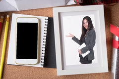 Woman picture in picture frame and blank smart phone and holiday Stock Image