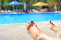 Woman& x27 ; pieds de s avec la piscine ensoleillée brouillée à l'arrière-plan Photo stock