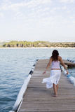 Woman on pier. Young beautiful woman walking on pier Stock Image