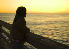 Woman on Pier. A woman watching the sunset from a pier Royalty Free Stock Photos