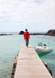 Woman on a pier. Middle-aged woman in casial clothes walks on a wooden pier in a small bay, Isla de LObos, Canary Islands Royalty Free Stock Photography
