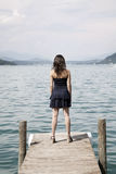 Woman on pier. Back view of an anonymous young woman in sexy dress standing at the end of a wooden pier, looking out over the water into the distance Royalty Free Stock Photo