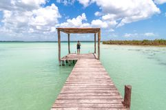 Woman on pier in Caribbean Bacalar lagoon, Mexico Stock Photos