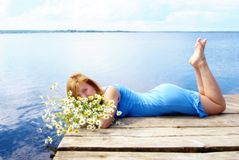 Woman on the pier lake. Woman with white daisy lie on the pier lake stock photos
