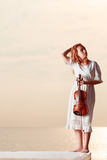 Woman on pier outside holding violin Stock Image