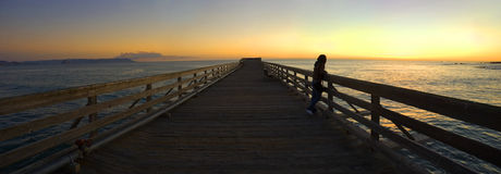 Woman on a Pier During Sunset. A woman watching the sunset from a pier Royalty Free Stock Photography
