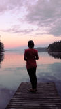 Woman on a pier. At sunset on lake Saimaa. Finland Royalty Free Stock Photo