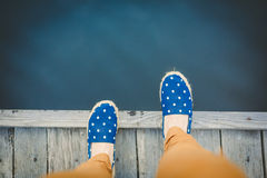 Woman on the pier takes a step into the water. From above stock image