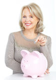 Woman with a pig bank Stock Photos