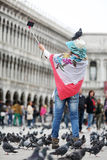 Woman with pigeons in Venice, selfie stick Stock Photography