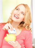 Woman with piggy bank and cash money Stock Image