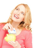 Woman with piggy bank and cash money Stock Images