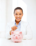 Woman with piggy bank and coin Royalty Free Stock Image