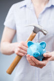 Woman with Piggy Bank and Hammer Stock Photography