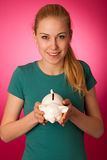 Woman with piggy bank in hands excited to safe save savings. Stock Photo