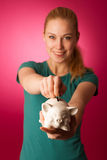 Woman with piggy bank in hands excited to safe save savings. Royalty Free Stock Image