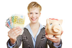 Woman with piggy bank holding euro money Stock Photography