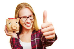 Woman with piggy bank holding thumbs up Stock Photo