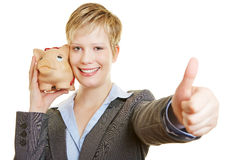 Woman with piggy bank holding thumbs up Royalty Free Stock Images