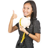 Woman with piggy bank showing thumbs up Stock Photography
