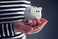 Woman with piggy coin bank. Home budget, finance and savings concept Stock Photos