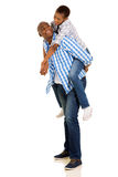 Woman piggybacking boyfriend. Pretty young african women piggybacking on her boyfriend over white background Royalty Free Stock Photo