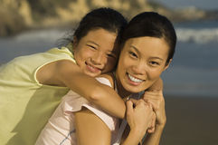 Woman Piggybacking Daughter On Beach Stock Photo