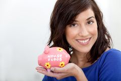 Woman with a piggybank Stock Images
