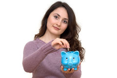 Woman with piggybank. A young attractive woman with blue piggy-bank Royalty Free Stock Images