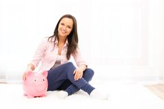 Woman with piggybank. Cheerful young woman sitting on a carpet with piggybank Royalty Free Stock Image
