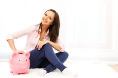 Woman with piggybank. Cheerful young woman sitting on a carpet with piggybank Royalty Free Stock Photos