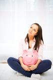 Woman with piggybank. Cheerful young woman sitting on a carpet with piggybank Stock Photography