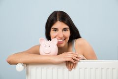 Woman with piggybank on radiator at home Royalty Free Stock Image