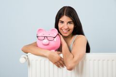 Woman with piggybank and radiator. Young Woman Leaning On Radiator With Pink Piggybank At Home Stock Photo