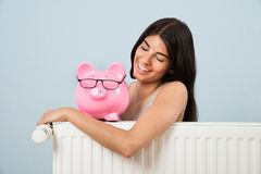 Woman with piggybank and radiator Stock Photos