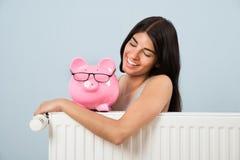 Woman with piggybank and radiator. Young Woman Leaning On Radiator With Pink Piggybank At Home Stock Photos