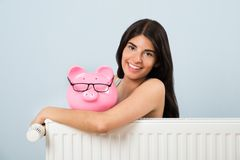 Woman with piggybank and radiator. Young Woman Leaning On Radiator With Pink Piggybank At Home Stock Photography