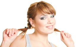 Woman with pigtails. Joyful attractive redhead girl hold for pigtails on white background Stock Photo