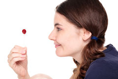 Woman in pigtails examining lollipop Royalty Free Stock Photos