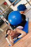 Woman with a Pilates  Ball. A beautiful young woman exericising with a blue pilates exercise ball Royalty Free Stock Photos