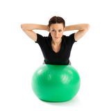 Woman with Pilates Ball. Pretty woman with hands behind head doing a pilates exercise using gym ball, isolated over a white background Royalty Free Stock Images