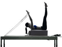 Woman pilates reformer exercises fitness. One caucasian woman exercising pilates reformer exercises fitness in silhouette on white backgound Stock Photo