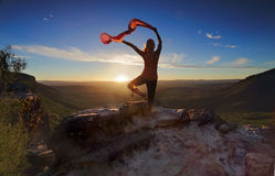 Woman Pilates Yoga balance with sheer flowing fabric. A woman balancing on one leg in mountain landscape, she has her arms outstretched holding sheer flowing stock photo