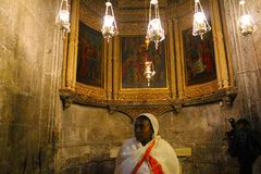 Woman pilgrim in The Church of the Holy Sepulchre, Christ`s tomb, in the Old City of Jerusalem, Israel stock photo