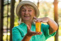 Woman with pill bottle smiling. Royalty Free Stock Photography